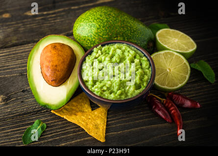 Guacamole in blue bowl with tortilla chips and lemon on natural wooden desk. - Stock Photo