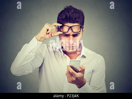 Young man with glasses having trouble seeing cell phone has vision problems. Bad text message. Human emotion perception - Stock Photo