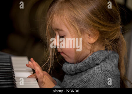 little girl playing on the keys of the piano, closeup - Stock Photo