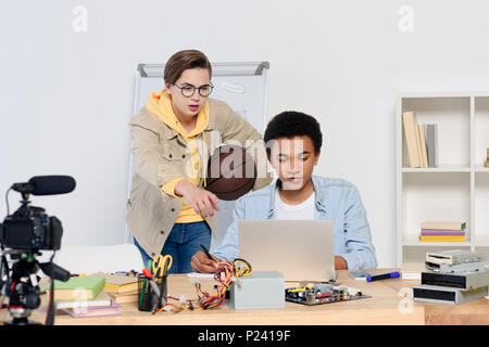 caucasian teenager pointing on something at laptop to african american friend at home - Stock Photo