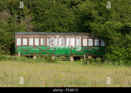 an old or vintage railway carriage coach made from wood and painted green being used as a coastal holiday home on the isle of wight at thorness bay. - Stock Photo