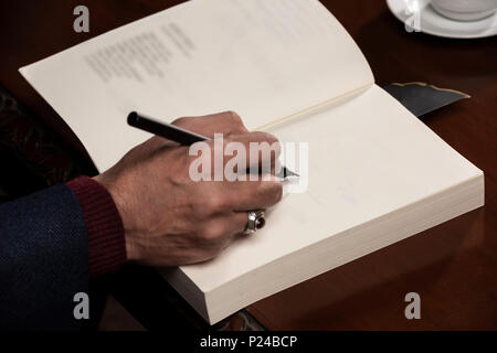 Man hand with pen writing on book. - Stock Photo