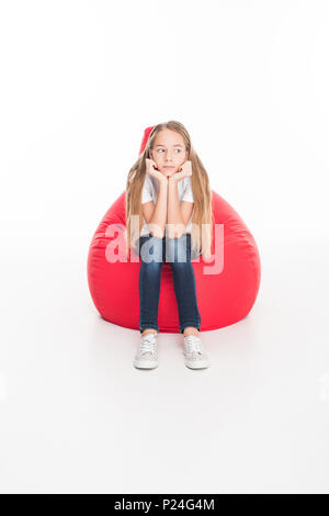 sad female youngster sitting in red bean bag chair, isolated on white - Stock Photo