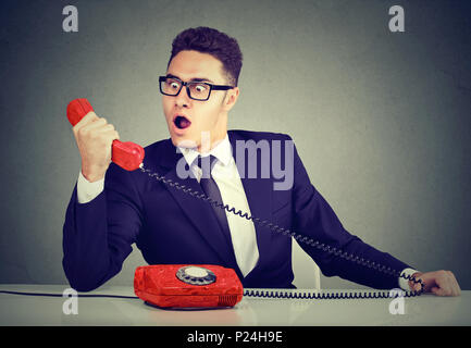 Shocked young business man receiving bad news on the phone sitting at desk in his office - Stock Photo