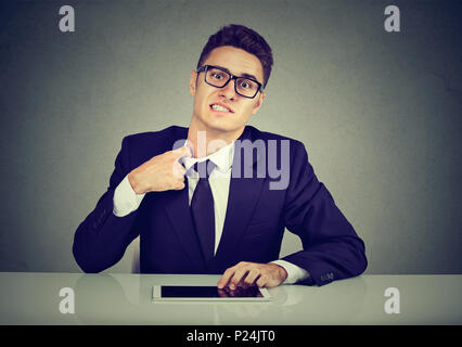 Stressed business man pulling his shirt on his neck uncomfortable with too tight tie and formal wear - Stock Photo