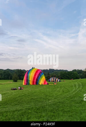 Biella, Italy, June 10, 2018 -Two hot air balloons being anchored and deflated after the flight at spring festival, June Pollone dal Cielo, Biella - Stock Photo