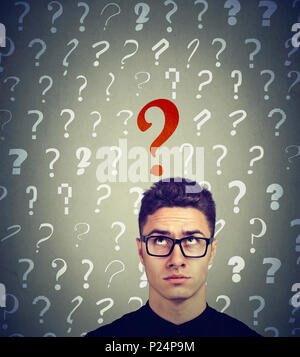 Serious business man looking up at a key red question - Stock Photo