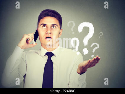 Misunderstanding and distant call concept. Upset annoyed young man talking on mobile phone has many questions isolated on gray background. - Stock Photo