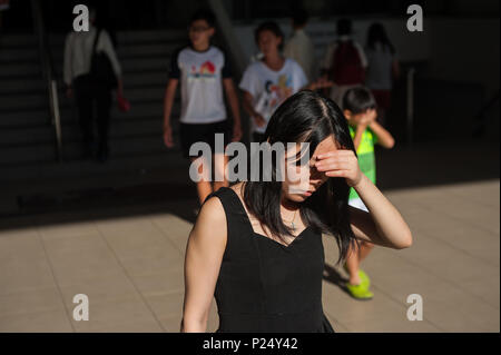 Singapore, Singapore, passersby leaving a shopping center - Stock Photo