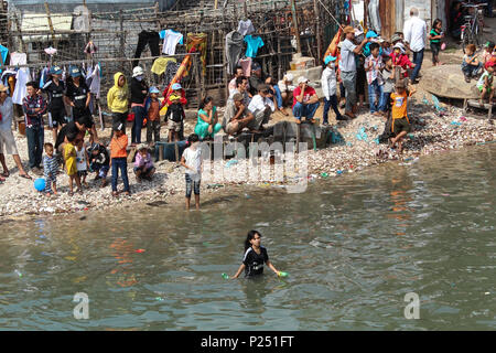 Phan Thiet , Vietnam - January 2014: Many people on waterside and in water looking in direction of traditional dragon boat race during new year in Pha - Stock Photo