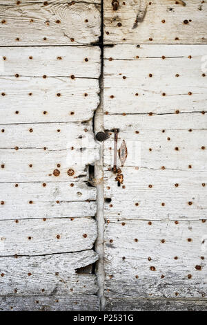 Old and weathered wooden door is closed, with metal handle and keyhole - Stock Photo