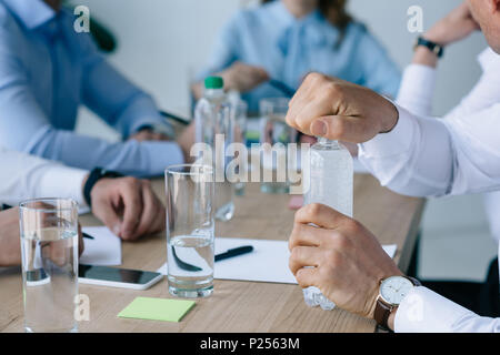 cropped shot of businessman opening bottle of water with colleagues at workplace near by  in office - Stock Photo