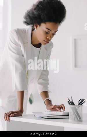 attractive african american businesswoman using calculator in office - Stock Photo