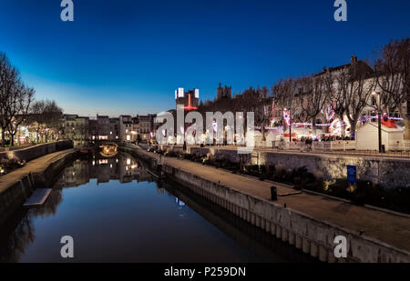 Canal de la Robine in the evening, Christmas fair - Stock Photo