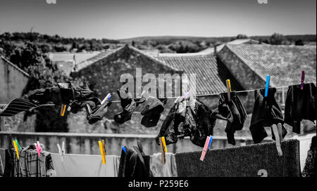 Coursan, view above the roofs and La Clape landscape from a roof-top terrace with clotheslines - Stock Photo