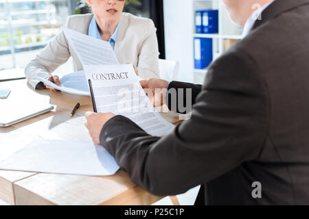 cropped shot of business colleagues discussing contract in office - Stock Photo