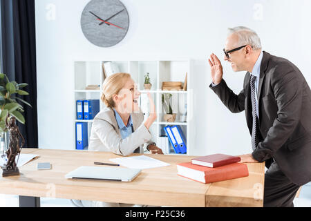 mature business colleagues giving high five at modern workplace - Stock Photo
