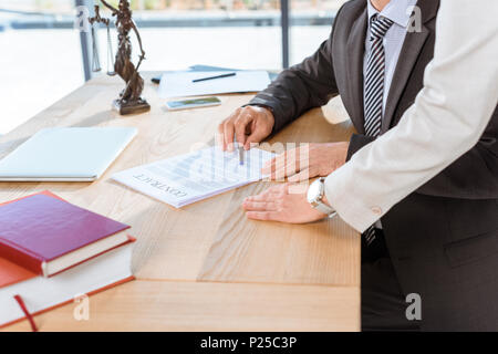 cropped shot of businesspeople discussing contract at workplace - Stock Photo