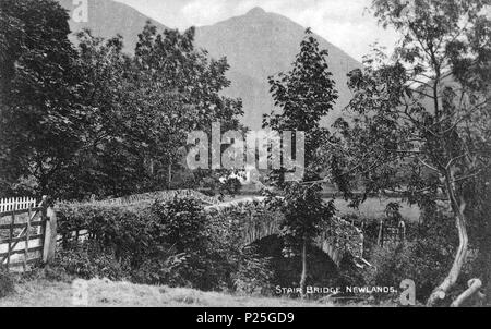.   This is a photo of listed building number 1144574.  English: Looking south-west over the Grade II listed early 19th-century bridge over Newlands Beck at Stair, in Newlands Valley, Cumbria, England. In the distance is the 2,090 ft. Causey Pike edging Newlands Valley. The photographer was Henry Mayson, who was born in Keswick and who set up a photographic studio there in the 1880s, producing postcards under the 'Mayson Series'. His work concerned the landscape and people of the Lake District. The geog-location is the approximate position of the camera. before 1921. Henry Mayson (1845-1921) b - Stock Photo