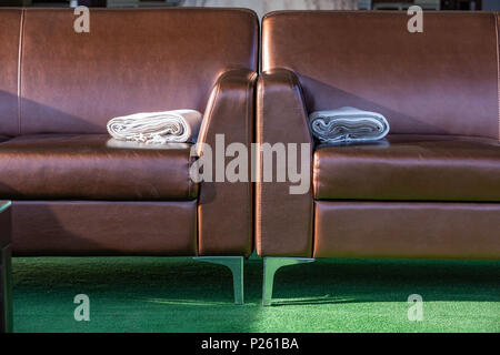 Close up modern elegant brown leather lounge sofa with woolen throw rug blanket on the arm. - Stock Photo