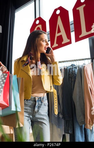 shocked young woman with shopping bags talking on smartphone and looking at sale sign - Stock Photo