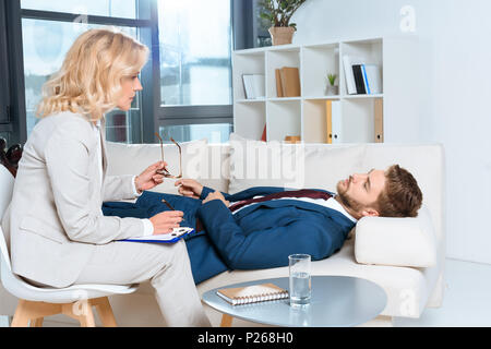 side view of psychologist talking with young businessman during psychotherapy - Stock Photo