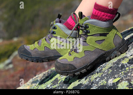 Hiking boots with rocks mountain background - Stock Photo