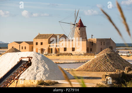 Pyramids of salt in front of Infersa windmill, on the coast connecting Marsala to Trapani, Trapani province, Sicily, Italy - Stock Photo