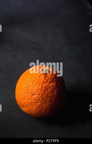 Orange on dirty chalkboard background - Stock Photo