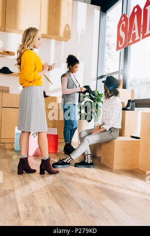 group of young shopping buddies spending time in clothing store - Stock Photo