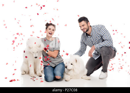 couple sitting with dogs under falling confetti on white, valentines day concept - Stock Photo