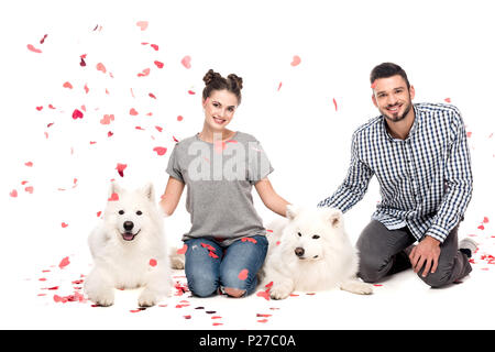 couple sitting with dogs under falling confetti isolated on white, valentines day concept - Stock Photo