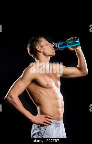 sportive muscular shirtless man drinking water from bottle isolated on black - Stock Photo