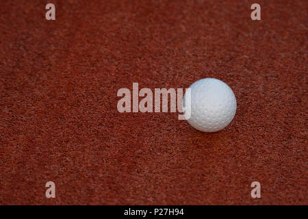 White ball for playing field hockey on the red grass background - Stock Photo