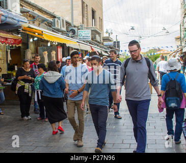 9 May 2018 Male Jewish students wearing skull caps and in conversation as they make their way through the busy Mahane Yehuda  market in Jerusalem - Stock Photo