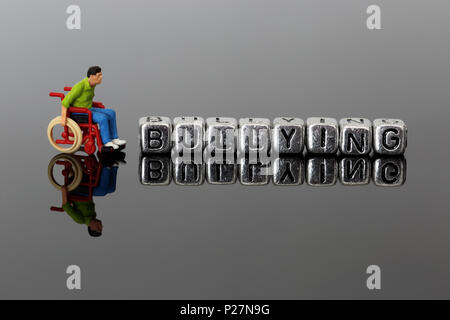 Miniature scale model man in a wheelchair with the word bullying on beads reflected on a dark background - Stock Photo
