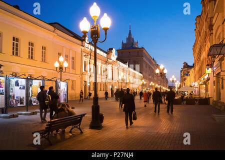 Moscow, Russia - September 21, 2017: People and historical building decorated by warm light at Arbat walking street during twilight with blue sky. - Stock Photo