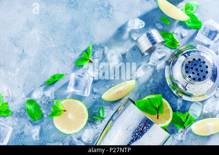 Shaker and bar accessories flat lay. Fresh mojito cocktail ingredients, mint, lime and ice cubes on a gray stone background. Summer drink concept with - Stock Photo
