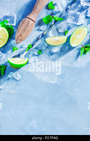 Mojito cocktail ingredients, mint, lime and ice cubes on a gray stone background with copy space. Lemon reamer or juicer in making summer drinks conce - Stock Photo