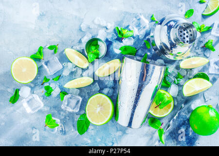Fresh mojito cocktail ingredients, mint, lime and ice cubes on a gray stone background. Shaker and bar accessories flat lay. Summer drink concept with - Stock Photo