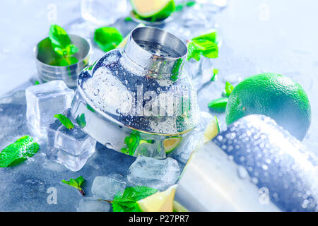 Shaker and bar accessories close-up. Mojito cocktail ingredients, mint, lime and ice cubes on a gray stone background. Summer drink concept with copy  - Stock Photo