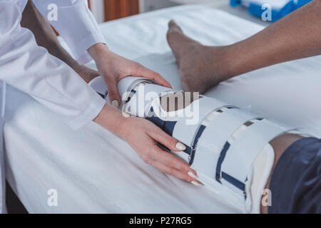 Cropped image of doctor checking african american patient leg brace - Stock Photo