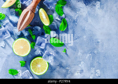 Summer drink header with mojito cocktail ingredients, mint, lime and ice cubes. Lemon reamer or juicer on a gray stone background with copy space. - Stock Photo