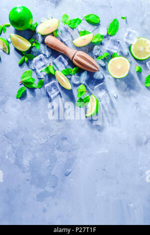 Lemon reamer or juicer with mint, lime and ice cubes. Mojito cocktail ingredients on a gray stone background with copy space. Summer drink concept sun - Stock Photo