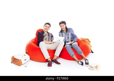 teenage students studying together while sitting on bean bags isolated on white - Stock Photo