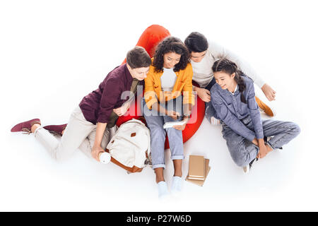 high angle view of group of teen students studying while sitting on bean bag isolated on white - Stock Photo