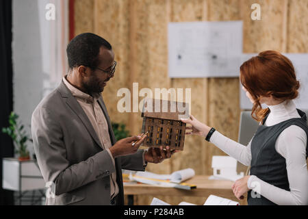 young architects discussing wooden house model at office - Stock Photo