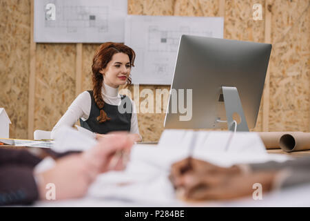 young female architect working with computer at office while colleagues drawong plans on foreground - Stock Photo