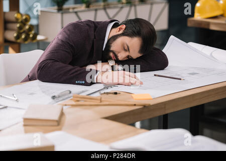 overworked young architect sleeping on building plans at workplace - Stock Photo