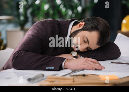 exhausted architect sleeping on building plans at workplace - Stock Photo
